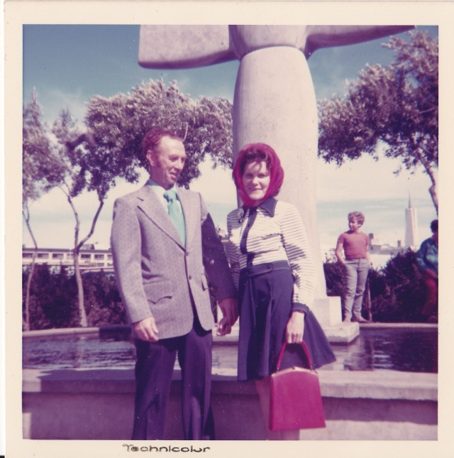 "Peter Doran and Lillian. ""This huge sculpture in the background was by Benny Bufino an Italian artist. The statue is of St. Francis""."