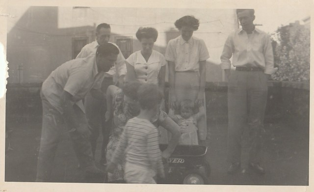 Mary Mahoney Doran is being helped out of the little wagon by her son-in-law, Walter.